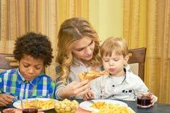 Pizza de alimentación de la mujer al niño fotos de archivo libres de regalías