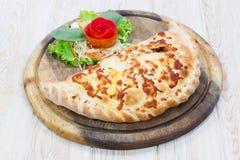 Pizza de Calzone en plato de madera Foto de archivo