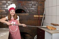 Pizza de cuisinière de petite fille vraie dans la pizzeria Photographie stock