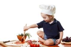 Pizza de cuisinier de petit garçon Plan rapproché d'isolement sur le blanc Photos libres de droits
