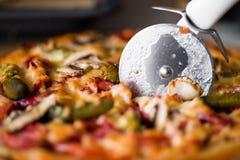 Pizza de découpage Images stock