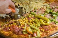 Pizza de découpage Photographie stock libre de droits
