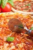 Pizza de découpage avec un pizza-couteau Images stock