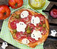 Pizza de Dia das Bruxas com as aranhas da azeitona da American National Standard dos fantasmas do queijo Fotos de Stock