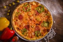 Pizza de la salchicha, de la pimienta y de las aceitunas en una tabla de madera fotos de archivo
