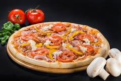 Pizza de luxe avec du mozzarella, salami, lard, oignon, tomates photographie stock