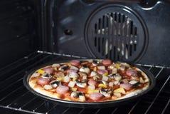 Pizza in de oven stock fotografie