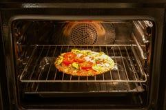 Pizza in de oven Royalty-vrije Stock Afbeeldingen