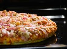 Pizza in de oven Stock Afbeelding