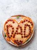 Pizza de pepperoni dans la forme de coeur et le mot de papa Photographie stock