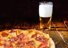 Pizza de pepperoni savoureuse sur la table en bois près d'un verre de bière Photo libre de droits