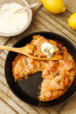 Pizza de pomme de terre avec les saumons et la crème dans la casserole noire Images libres de droits