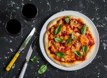 Pizza de potiron et deux verres de vin rouge sur le fond foncé Image libre de droits
