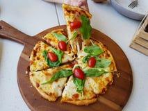 Pizza de queso cuatro con la ensalada de cohete y el tomate de cereza en fondo de madera de la placa imagenes de archivo
