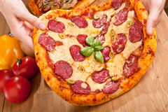 Pizza de salami dans des mains Photo stock