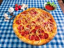 Pizza de salami et de jambon avec du fromage et l'oignon photographie stock libre de droits