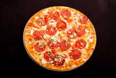 Pizza de salchichones caseosa caliente en fondo negro Imágenes de archivo libres de regalías