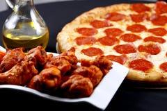 Pizza de salchichones con las alas de pollo fotos de archivo