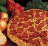Pizza de salchichones con los tomates y el fondo de las cebollas Fotos de archivo