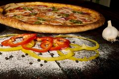 Pizza de salchichones con pimientas de chile del jamón y del jalapeno en la tabla de madera vieja imagen de archivo