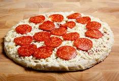 Pizza de salchichones congelada en una tarjeta de corte fotografía de archivo libre de regalías