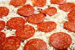 Pizza de salchichones congelada en una tarjeta de corte fotografía de archivo