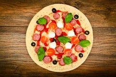 Pizza de salchichones cruda con la salchicha, queso, mozzarella, aceitunas y Fotos de archivo