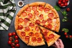 Pizza de salchichones en un fondo concreto negro fotografía de archivo libre de regalías