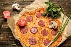 Pizza de salchichones en una tabla de madera la visión desde el top Imagen de archivo libre de regalías