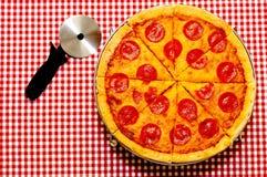 Pizza de salchichones entera rebanada con el cortador fotos de archivo