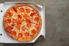 Pizza de salchichones sabrosa en una caja en fondo concreto marrón Vista superior de la pizza de salchichones caliente Con el esp imagen de archivo