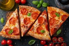 Pizza de salchichones sabrosa y cocinar albahaca de los tomates de los ingredientes en fondo concreto negro Vista superior de la  foto de archivo libre de regalías