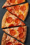 Pizza de salchichones sabrosa y cocinar albahaca de los tomates de los ingredientes en fondo concreto negro Vista superior de la  imagen de archivo