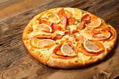 Pizza de Salmone en la tabla de madera. Imagen de archivo
