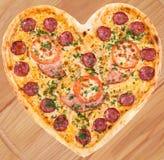 Pizza de viande avec du jambon dans la forme de coeur pour la valentine Photographie stock libre de droits