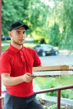 Pizza dealer with pizza boxes brings the order royalty free stock photography