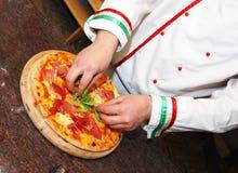 Pizza del condimento del cuoco fotografia stock
