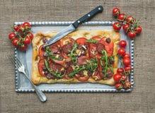 Pizza del cuadrado de la carne de Ristic con los tomates de cereza y el arugula sobre a Imagen de archivo