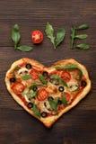 Pizza del día de tarjetas del día de San Valentín en forma del corazón con amor del texto en fondo de madera oscuro Fotografía de archivo libre de regalías