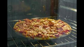 Pizza del prosciutto e del fungo che cucina nel lasso di tempo del forno video d archivio