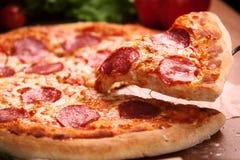 Pizza del salami en la tabla Imagenes de archivo