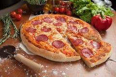Pizza del salami en la tabla Foto de archivo libre de regalías