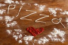 Pizza del texto escrito de la mayonesa y de la harina en la tabla de madera Imagenes de archivo