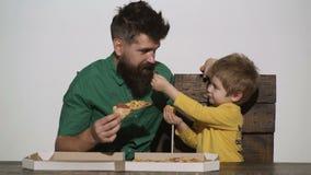 Pizza deliciosa antropófaga com menino da criança Menino caucasiano pequeno bonito que come a pizza com o homem farpado isolado n video estoque