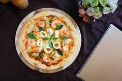 Pizza deliciosa com marisco no suporte de madeira, vista superior Imagens de Stock Royalty Free