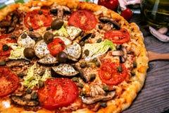 Pizza deliciosa com salame, cogumelos do queijo e azeitonas fotos de stock royalty free