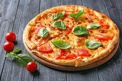 Pizza deliciosa con los tomates de cereza y la albahaca fresca Foto de archivo