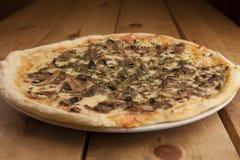 Pizza deliciosa de la seta en una tabla de madera foto de archivo