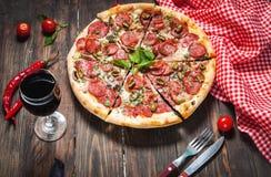 Pizza deliciosa, vidro de vegetais do vinho e especiarias na tabela de madeira imagem de stock royalty free