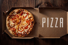 Pizza in the in delivery box on the wood Stock Photography